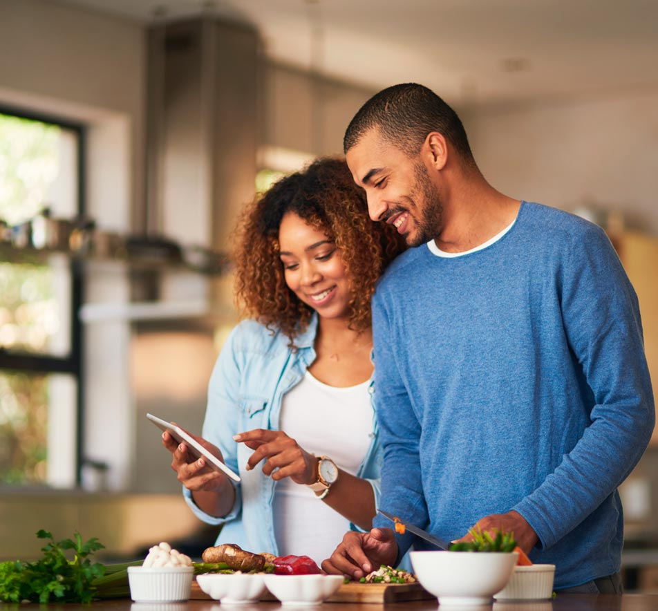 Happy couple in kitchen on a mobile device