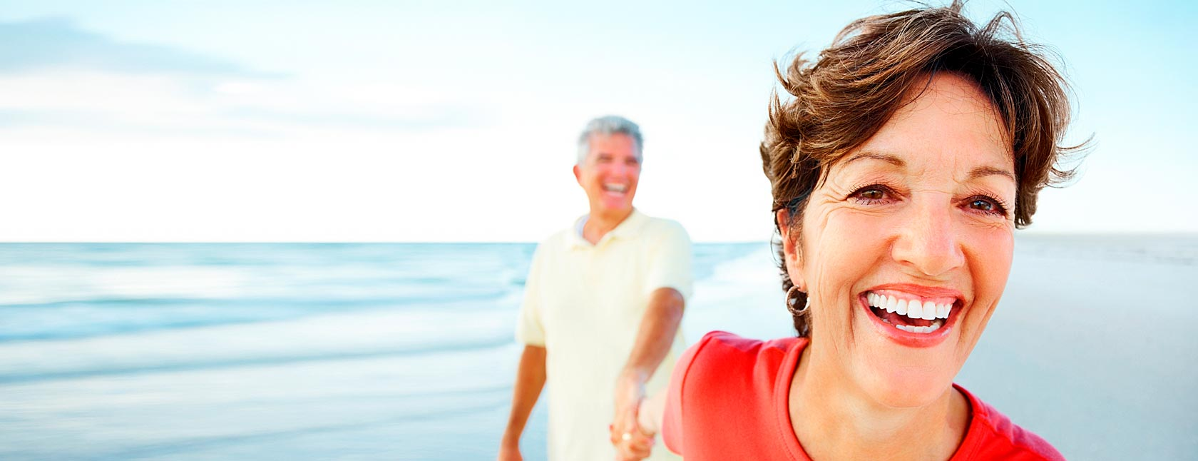 Older couple laughing on beach