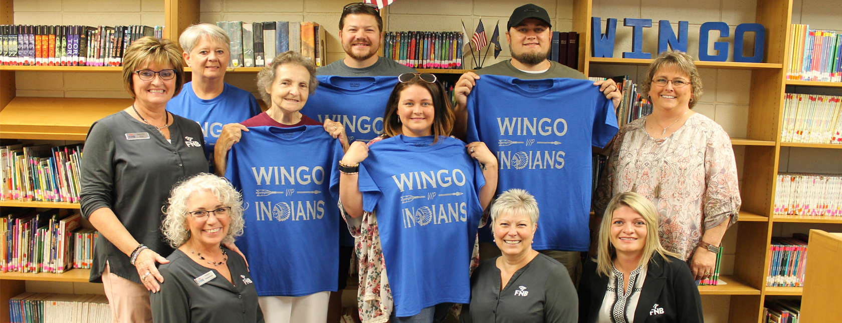 FNB bank employees with Wingo Indians friends holding up Wingo Indians shirts